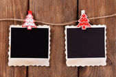 Blank photo frames and Christmas decor on rope, on wooden background — Stock Photo