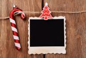 Blank photo frame and Christmas decor on rope, on wooden background — Stock Photo