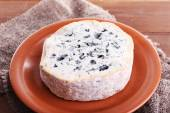 Blue cheese on earthenware dish on burlap cloth and wooden table background — Stock Photo