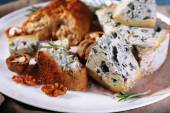 Blue cheese with sprigs of rosemary, bread and nuts on plate with burlap cloth, closeup — Stock Photo