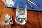 Glass of water with ice on napkin on wooden table background — Stock Photo