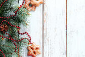 Cookies with sprig of Christmas tree on color wooden background — Stock Photo