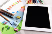 Tablet PC with office supplies on desktop background — Stock Photo