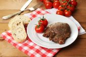 Roasted meat and vegetables on plate, on wooden table background — Stock Photo