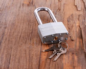 Padlock with keys on wooden background — Stock Photo