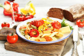 Pasta salad with pepper, carrot and tomatoes on wooden table background — Stock Photo