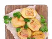Baked potato with bacon on wooden cutting board, isolated on white — Stock Photo