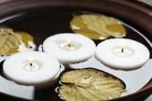 Boom witte kaarsen zweven met bladeren op water in kom — Stockfoto