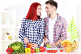 Happy couple cut vegetables in kitchen — Stock Photo