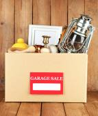 Box of unwanted stuff ready for a garage sale on wooden background — Foto Stock