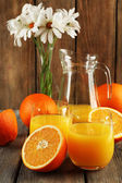 Glass of orange juice with slices and flowers on rustic wooden background — 图库照片