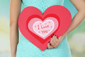 Girl holding Valentine card on bright background — Foto de Stock