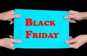 Women's hands holding advertising with Black Friday text on it isolated on black — Stock Photo