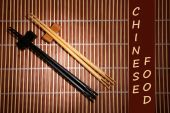 Pair of chopsticks and Chinese Food text on brown bamboo mat background — 图库照片