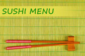 Pair of chopsticks and Sushi Menu text on green bamboo mat background — 图库照片