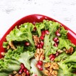 Fresh salad with greens, garnet and spices on plate on table close-up — Stock Photo #61893305