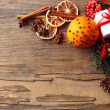 Orange with present box, spices, slices of dried lemon and sprigs of Christmas tree on rustic wooden background — Stock Photo #61895021