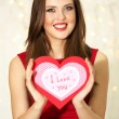 Smiling girl holding Valentines card with greetings on lights background — Stock Photo #61896007