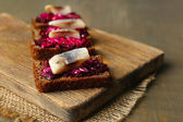 Canape herring with beets on rye toasts, on wooden board, on wooden table background — Stock Photo