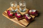 Canape herring with beets on rye toasts, on wooden board, and glass of vodka on wooden table background — Stock Photo