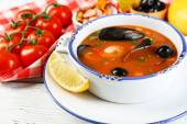 Tasty soup with shrimps, mussels, tomatoes and black olives in bowl on wooden background — Stock Photo