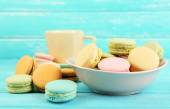 Assortment of gentle colorful macaroons in colorful bowl and mug with milk on color wooden background — Stock Photo