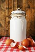 Milk can with eggs and eggshell on napkin on rustic wooden background — Stock Photo