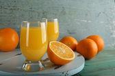 杯橙汁与切片上颜色木制背景 — 图库照片