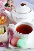 Composition with colorful macaroons, teapot and up of tea on color wooden background — Stock Photo