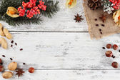 Christmas pine sprig with spices on color wooden background — Stock Photo