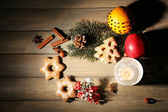 Cookies with fruits, spices and candle lantern on wooden background — Stock Photo