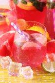 Różowa lemoniada w okularach i dzban na jasnym tle — Zdjęcie stockowe