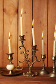 Retro candlesticks with candles on wooden background — Stock Photo