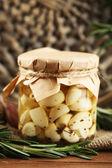 консервированный чеснок в стеклянной фляге и плетеной циновке и ветвях розмарина, на деревянном фоне — Стоковое фото