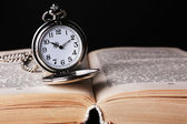 Silver pocket clock and book on wooden table — Stock Photo