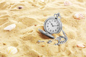 Silver pocket clock on sand background — Zdjęcie stockowe
