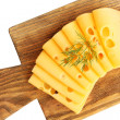 Sliced cheese with dill on wooden cutting board isolated on white background — Stock Photo #62019855