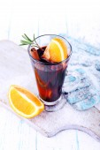 Glass of hot mulled wine with pieces of orange on cutting board with mittens and color wooden table background — Stock Photo