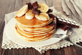 Stack of delicious pancakes with chocolate, honey and slices of banana on plate and napkin on wooden table background — Stockfoto