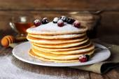 Stack of delicious pancakes with powdered sugar and berries on plate and napkin on wooden background — Stock Photo