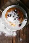 Stack of delicious pancakes with powdered sugar and berries on plate and napkin on wooden table background — Stock Photo