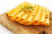 Sliced cheese with dill on wooden cutting board isolated on white background — Stock Photo