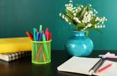 Desk with books and flowers — Stockfoto