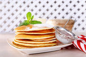 Stack of pancakes on plate with bank of jam on table and wooden lattice background — Stock Photo