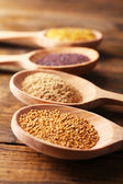 Mustard seeds, powder and sauce in wooden spoons on wooden background — Stock Photo