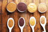 Mustard seeds, powder and sauce in spoons  and bowls on wooden background — Stock Photo