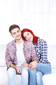 Couple sitting together in sofa — Stock Photo