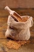 Mustard seeds in bag on  wooden background — Stock Photo