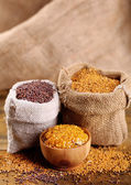 Mustard seeds in bags and sauce in bowl on  wooden background — Stock Photo