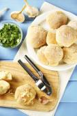 Fresh homemade bread buns from yeast dough on wooden cutting board, on color wooden background — Stock Photo